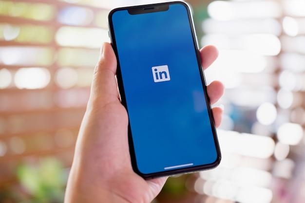 Eine frau hält iphone xs mit linkedin-anwendung auf dem bildschirm. linkedin ist eine app zum teilen von fotos für smartphones. Premium Fotos