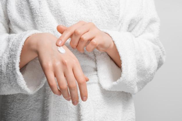Eine frau in einem gewand bedeckt ihre hände mit feuchtigkeitscreme. Premium Fotos
