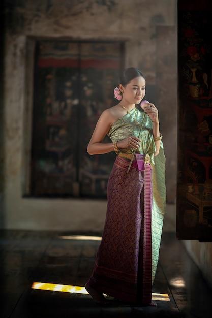 Eine frau in einem thailändischen kleid hält eine lotusblume in der hand, um die mönche im tempel vorzustellen. Premium Fotos