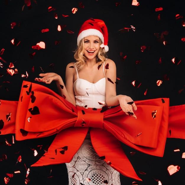 Eine frau in einem weißen kleid als geschenk auf einem schwarzen hintergrund wird in ein festliches band in fliegenden konfetti gewickelt. Premium Fotos