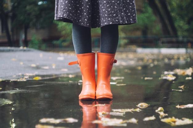 Eine frau in leuchtend rosa gummistiefeln (gummistiefel) unter dem regen. herbst-konzept Premium Fotos
