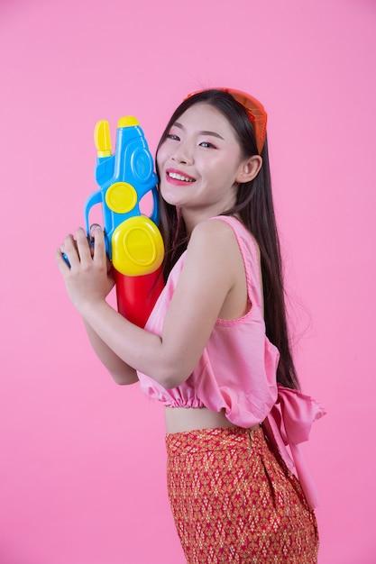 Eine frau kleidete in der traditionellen thailändischen volkskleidung an, die einen wasserwerfer auf einem rosa hintergrund hält. Kostenlose Fotos