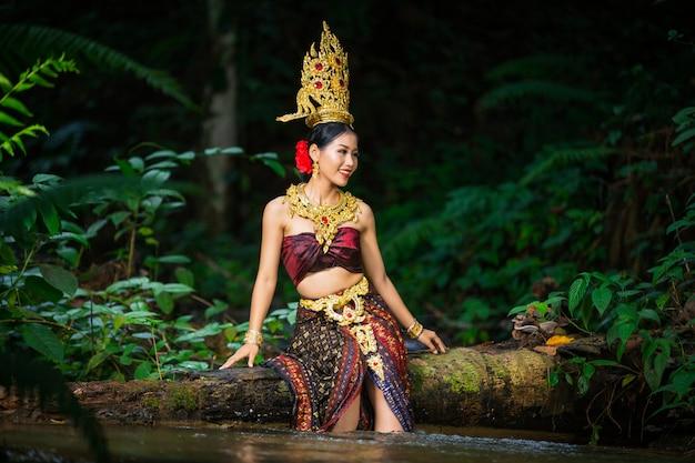 Eine frau kleidete sich mit einem alten thailändischen kleid am wasserfall an. Kostenlose Fotos