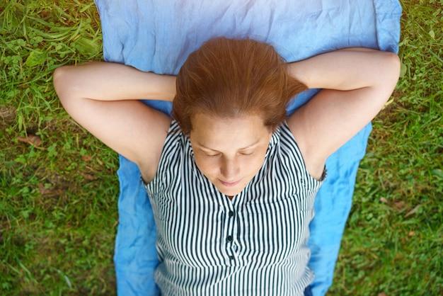 Eine frau liegt mit geschlossenen augen entspannt im gras Kostenlose Fotos