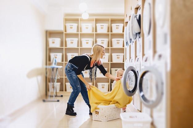 Eine frau mit einem kind legt die bettwäsche in die wäsche Premium Fotos