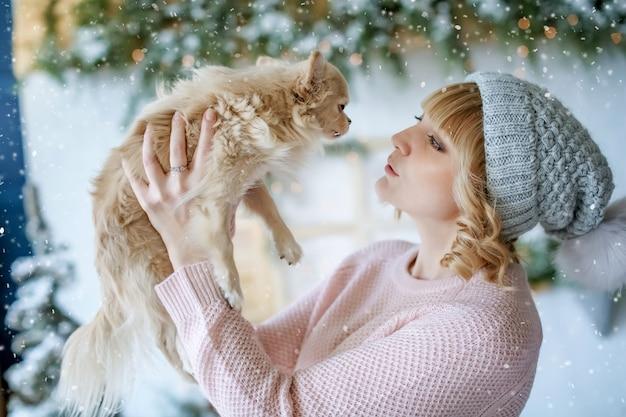 Eine frau mit einem welpen der kleinen rasse in ihren armen in einem weihnachtsfoto auf dem hintergrund der winterlandschaft. Premium Fotos
