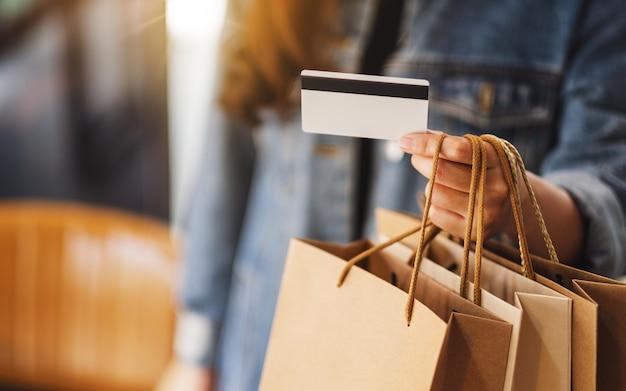 Eine frau mit einkaufstüten, die eine kreditkarte für den kauf halten und verwenden Premium Fotos