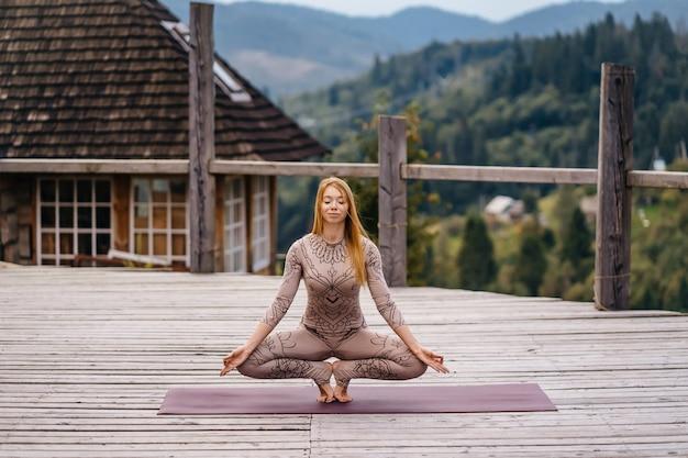 Eine frau praktiziert yoga am morgen auf einer terrasse an der frischen luft. Kostenlose Fotos