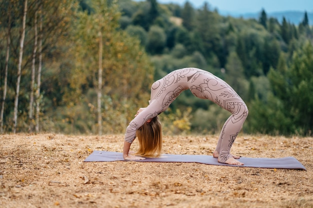 Eine frau praktiziert yoga am morgen in einem park an der frischen luft. Kostenlose Fotos