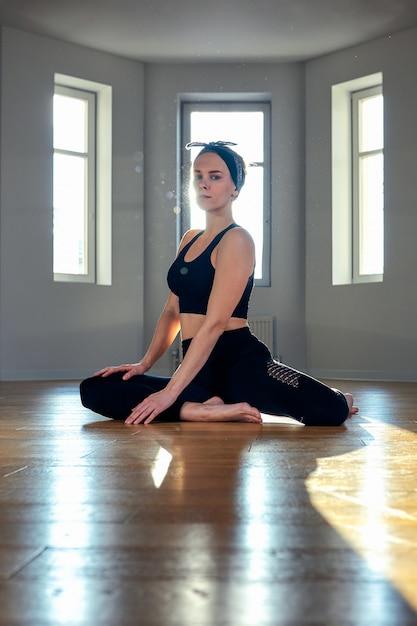 Eine frau praktiziert yoga in einem fitnessraum im morgengrauen Premium Fotos