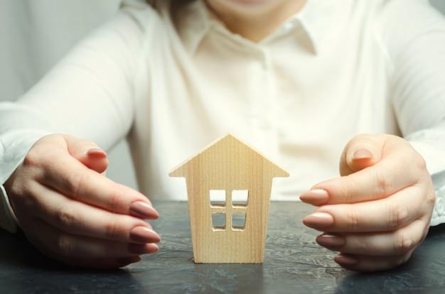 Eine frau schützt ein miniaturholzhaus. Premium Fotos