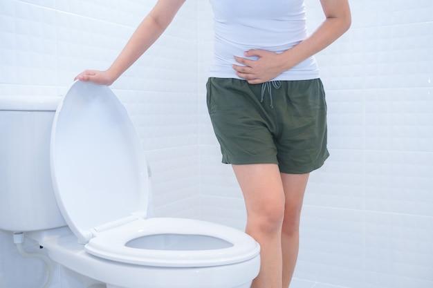 Eine frau sitzt auf toilette mit durchfall oder konzept der verstopften schmerz. Premium Fotos