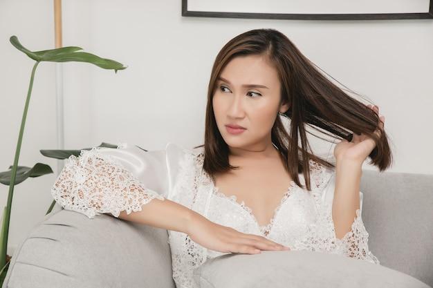 Eine frau sitzt benommen und abgelenkt auf dem grauen sofa zu hause mädchen zieht ihre haare mit der hand Premium Fotos