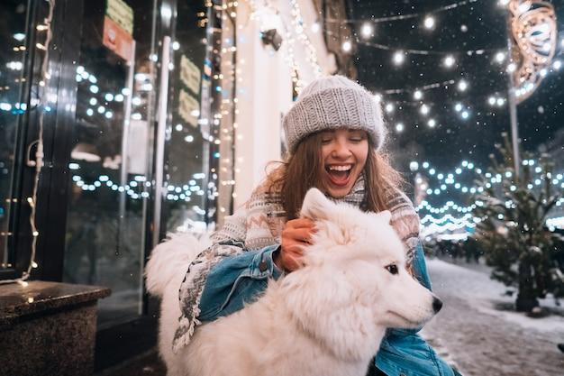 Eine frau umarmt ihren hund auf einer nachtstraße. Kostenlose Fotos