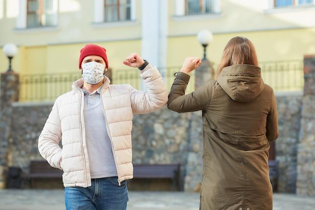 Eine frau und ein mann in medizinischen masken stoßen an die ellbogen, anstatt sie mit einer umarmung zu begrüßen Premium Fotos