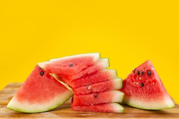 Eine frisch geschnittene wassermelone in vorderansicht, weich und saftig auf gelber fruchtsommerfarbe Kostenlose Fotos