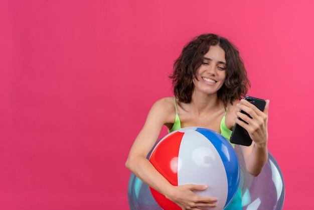 Eine fröhliche junge frau mit kurzen haaren in der grünen erntespitze, die aufblasbaren ball lächelt und das handy betrachtet Kostenlose Fotos