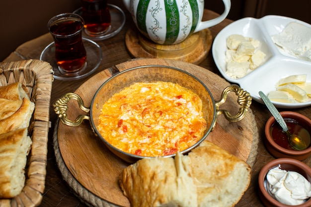 Eine front nahaufnahme ansicht gekochte eier mit roten tomaten in der metallpfanne zusammen mit heißem tee und brotstücken Kostenlose Fotos