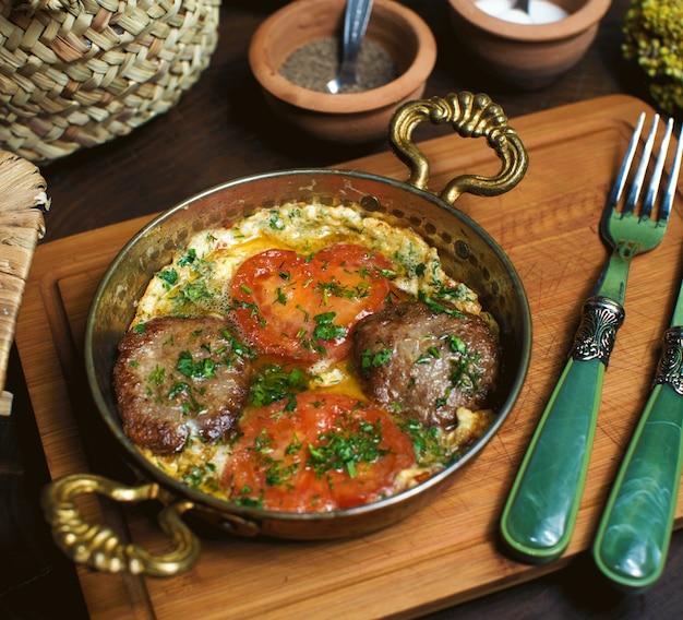 Eine front nahaufnahme ansicht gekochte eier zusammen mit roten tomaten in der metallpfanne auf dem braunen holzschreibtisch Kostenlose Fotos