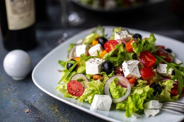 Eine frontansicht griechenland salat geschnittener gemüsesalat mit tomaten gurken weißen käse und oliven in weißen platte vitamin gemüse Kostenlose Fotos