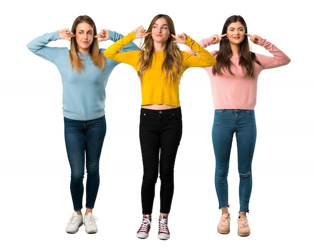 Eine ganzaufnahme einer gruppe von personen mit bunter kleidung, die beide ohren bedeckt Premium Fotos