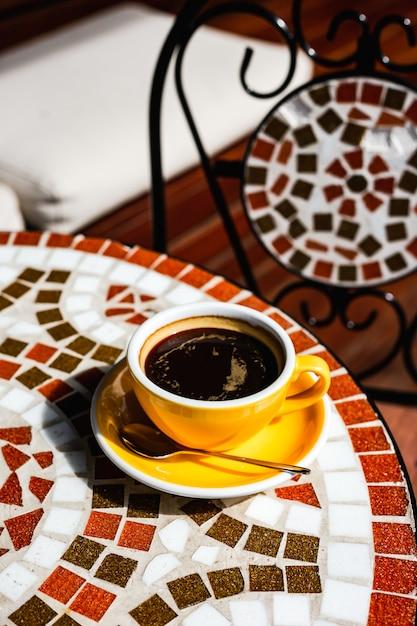Eine gelbe tasse schwarzen kaffees auf einer untertasse, einem löffel, auf einem mosaiksteintisch einer kaffeeterrasse an einem sonnigen tag Premium Fotos