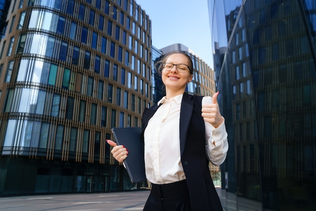Eine geschäftsfrau steht tagsüber mit einem laptop in anzug und brille vor einem bürogebäude. Kostenlose Fotos
