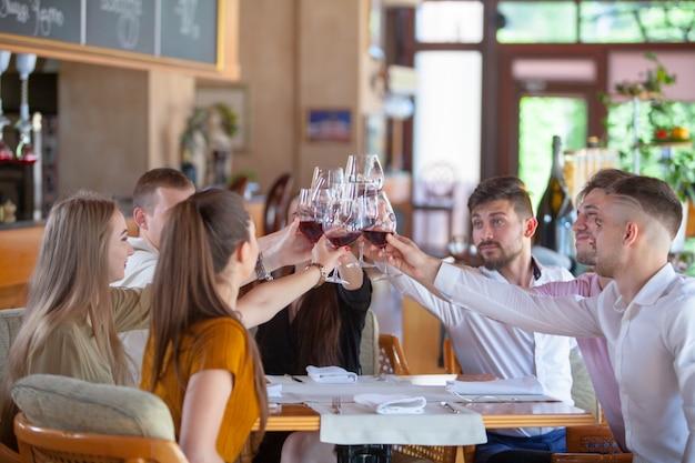Eine gesellschaft von freunden feiert das treffen in einem restaurant. Premium Fotos