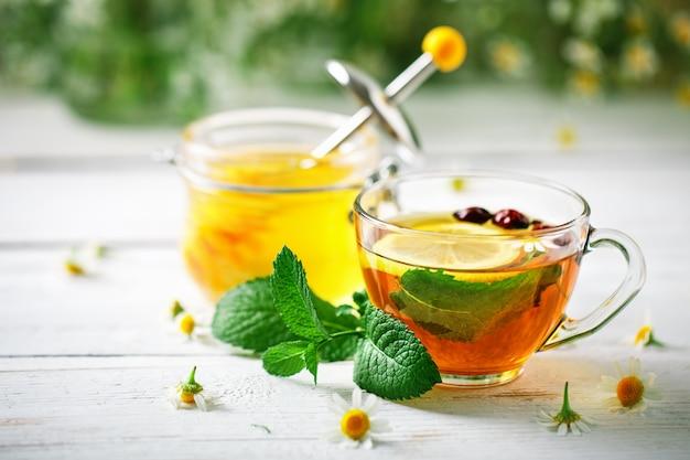 Eine gesunde tasse tee, ein glas honig und blumen. Premium Fotos
