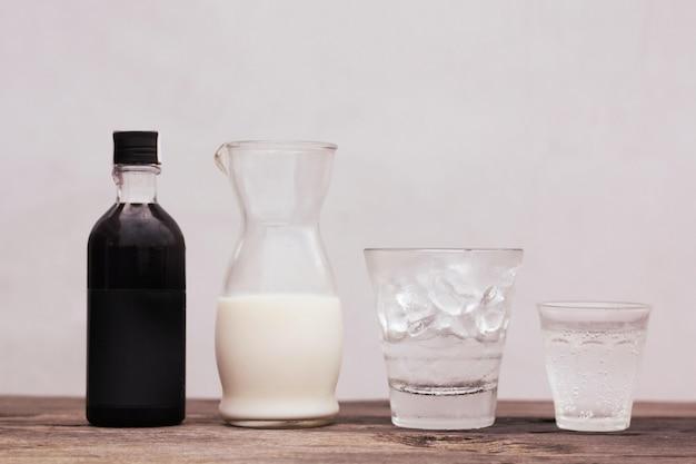 Eine glasflasche mit einer schwarzen flüssigkeit und einer glaskaraffe milch Kostenlose Fotos