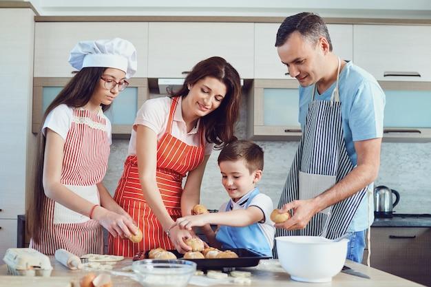 Eine glückliche familie bereitet das backen in der küche vor. Premium Fotos