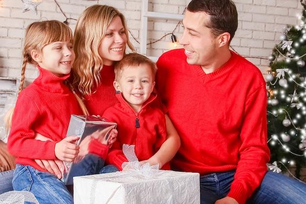 Eine glückliche familie mit geschenken an weihnachten Premium Fotos