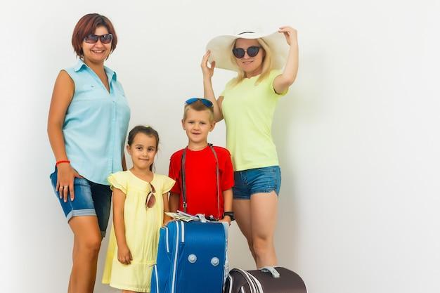 Eine glückliche familie mit ihren koffern auf einem weiß Premium Fotos