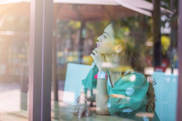 Eine glückliche frau, die am fenster in einem café sitzt und nach draußen schaut Premium Fotos
