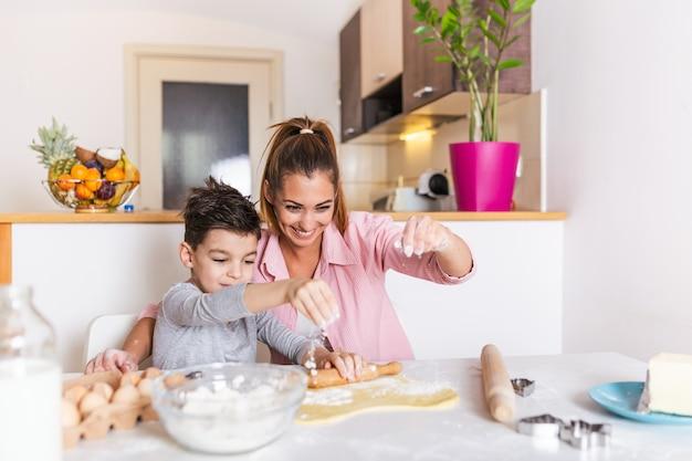 Eine glückliche, liebevolle familie bereitet gemeinsam eine bäckerei vor. mutter und kind sohn junge kochen kekse und haben spaß in der küche. Premium Fotos
