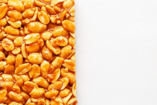 Eine große fliese des gebratenen erdnussriegels in einer süßen melasse. kozinaki nützliche und leckere süßigkeiten aus dem osten Premium Fotos