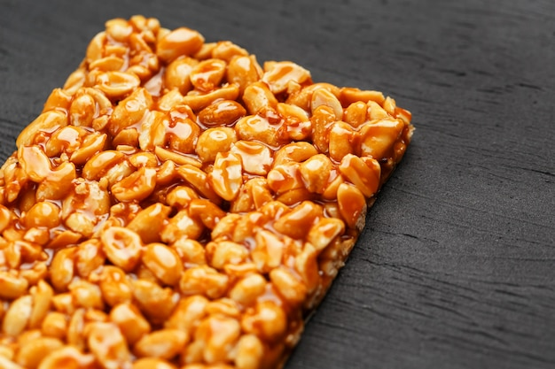 Eine große goldene fliese mit erdnüssen, eine tafel mit süßer melasse. kozinaki nützliche und leckere süßigkeiten aus dem osten Premium Fotos