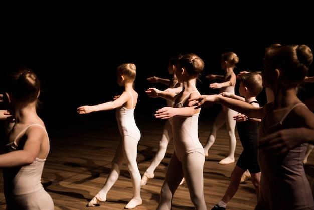 Eine große gruppe kinder, die das ballett proben und tanzen Premium Fotos