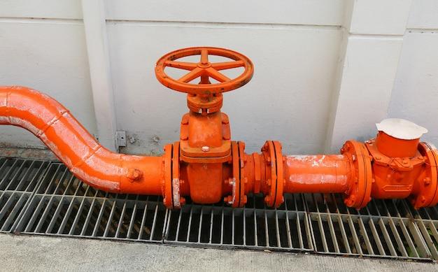 Eine große orange farbwasserversorgungshauptrohrleitung mit einem absperrventil gegen eine betonmauer. Premium Fotos