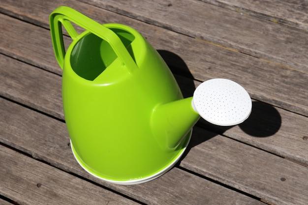 Eine grüne plastikgießkanne. Kostenlose Fotos