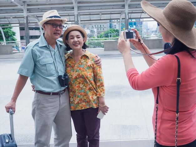 Eine gruppe ältere leute, die fotos beim reisen in die stadt stehen und machen Premium Fotos
