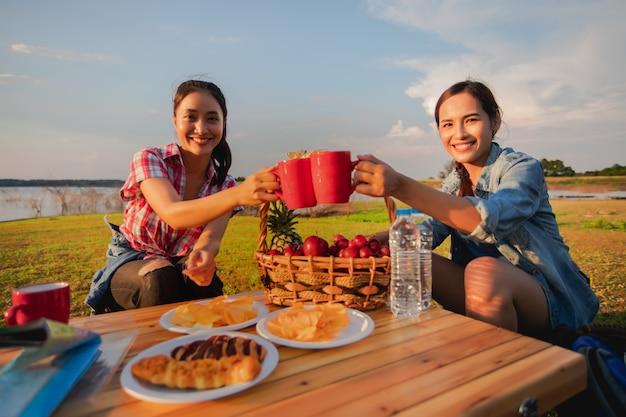 Eine gruppe asiatischer freunde, die kaffee trinken und in den sommerferien ein picknick machen. sie sind glücklich und haben spaß an den feiertagen. Premium Fotos