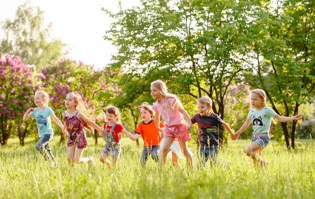 Eine gruppe glückliche kinder von jungen und von mädchen laufen in den park auf dem gras an einem sonnigen sommertag Premium Fotos