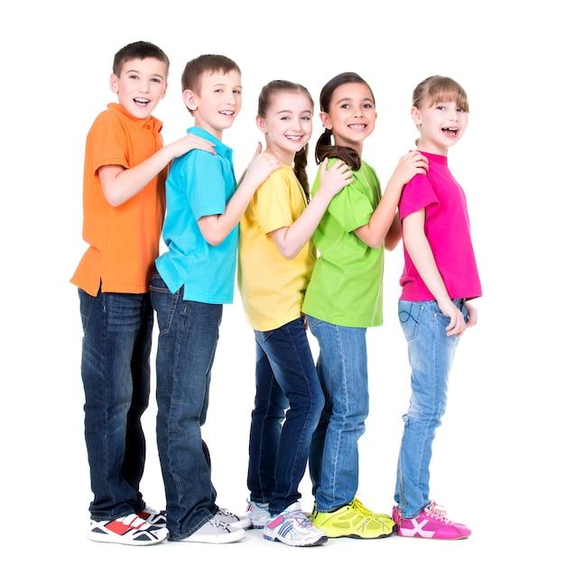 Eine gruppe glücklicher kinder in bunten t-shirts steht hintereinander und legt hände auf die schultern auf weißem hintergrund. Kostenlose Fotos