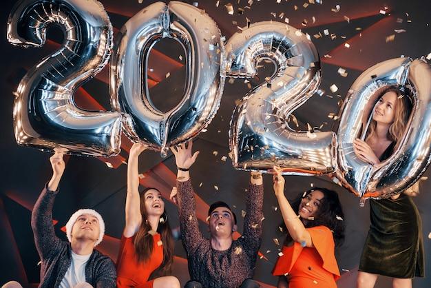 Eine gruppe junge schöne multinationale leute des spaßes, die konfettis an einer party werfen. frohes neues jahr. Premium Fotos