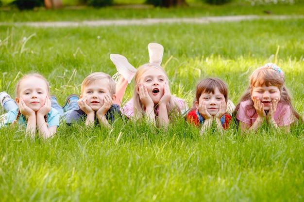 Eine gruppe kinder, die in den park auf einem grünen gozon spielen und laufen. Premium Fotos