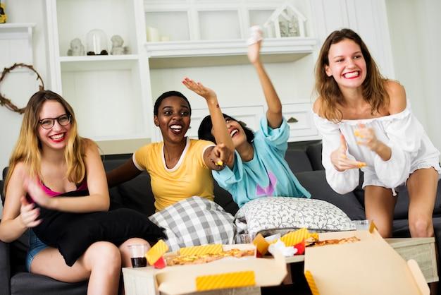 Eine gruppe verschiedene freundinnen, die auf der couch zusammen isst pizza sitzen Premium Fotos