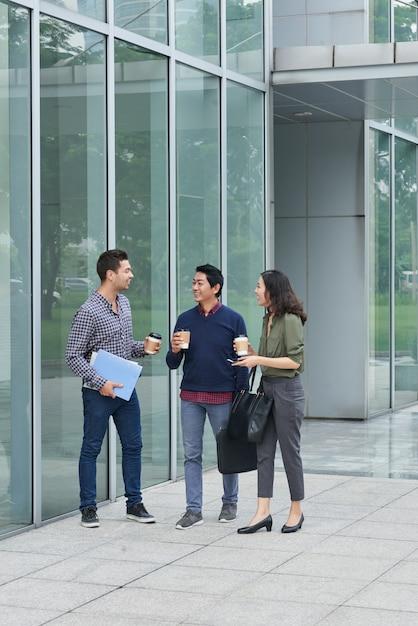 Eine gruppe von drei kollegen, die draußen mit mitnehmerkaffee an einer mittagspause waalking sind Kostenlose Fotos