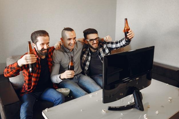 Eine gruppe von fans schaut fußball im fernsehen Kostenlose Fotos