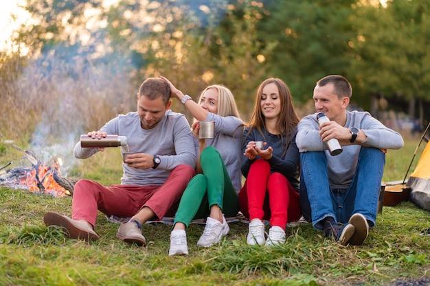 Eine gruppe von freunden genießt an einem kühlen abend am waldfeuer ein wärmendes getränk aus einer thermoskanne. fun time camping mit freunden Premium Fotos